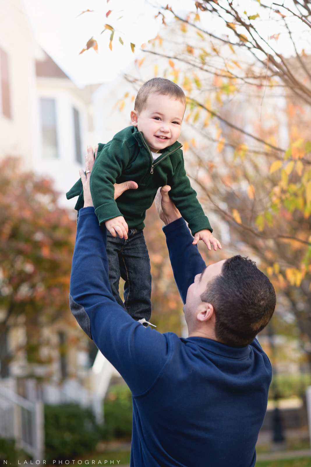 Dad throwing his happy son up in the air. Lifestyle family portrait by N. Lalor Photography. Fairfield County, Connecticut.