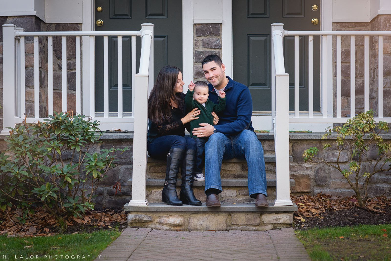 On the steps of their house. Lifestyle family portrait by N. Lalor Photography. Stamford, Connecticut.