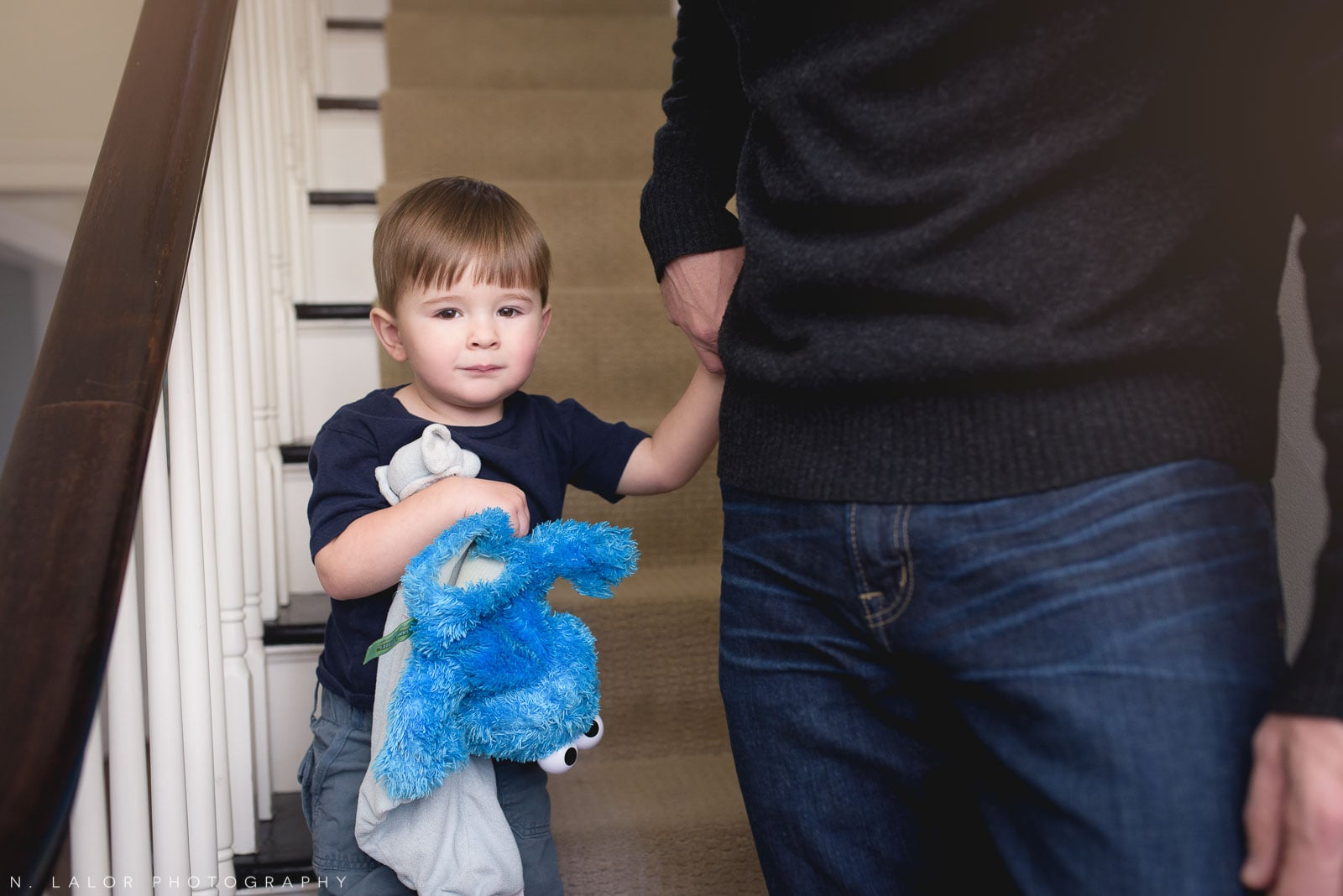 Toddler son holding his father's hand on the stairs. At-home lifestyle portrait by N. Lalor Photography.