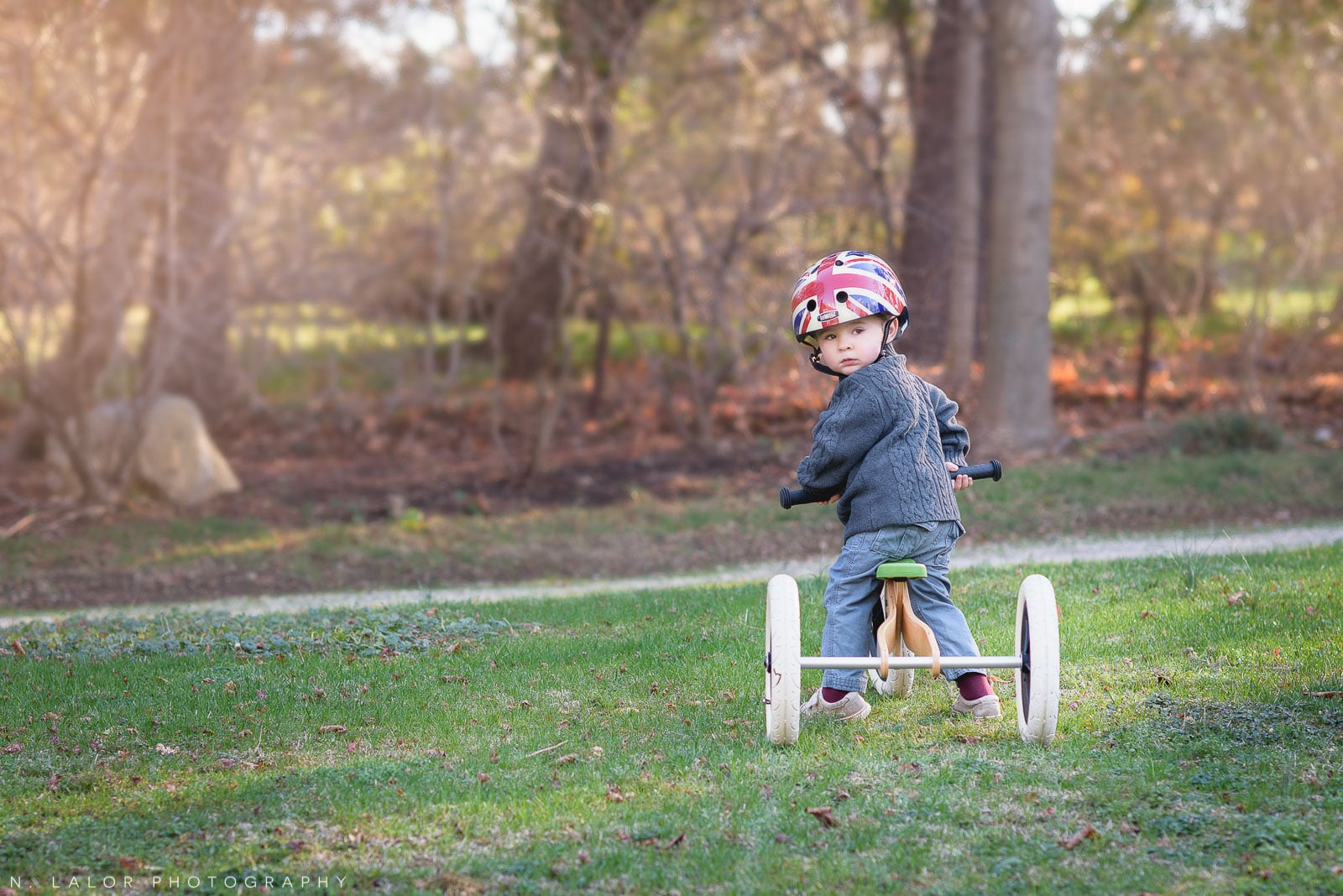 2-year old boy on his tricycle. Lifestyle outdoor portrait by N. Lalor Photography.
