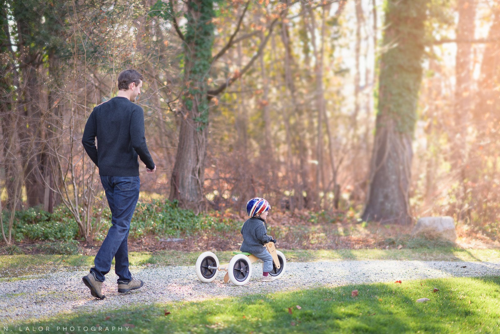 Dad with his toddler son riding a tricycle. Lifestyle portrait by N. Lalor Photography.