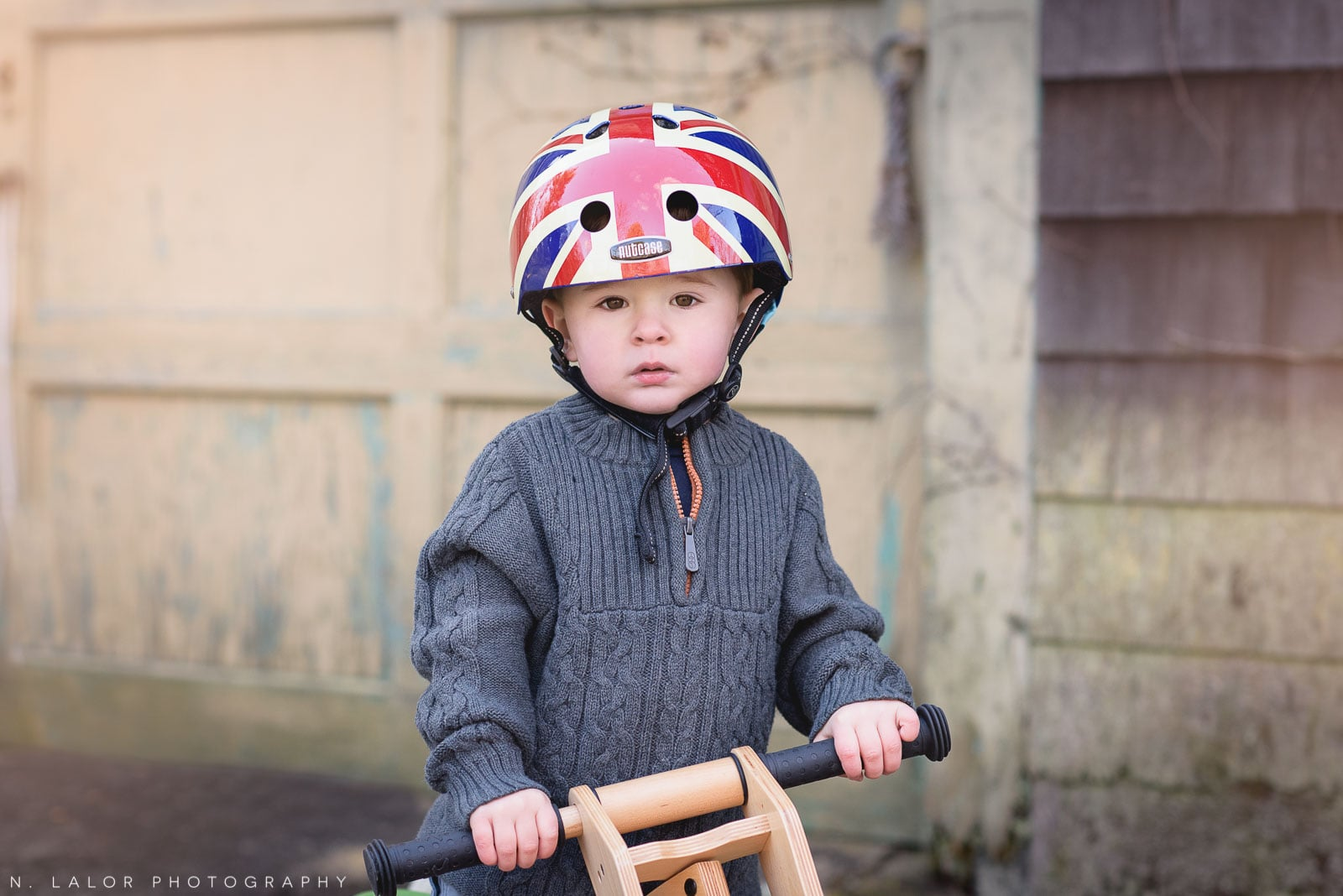 Two-year old toddler portrait with his tricycle, wearing a helmet. Lifestyle portrait by N. Lalor Photography. Norwalk, Connecticut.