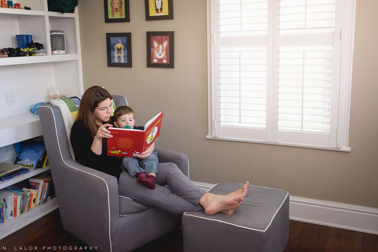 Mom reading a Curious George book to toddler son. In-home lifestyle photo by N. Lalor Photography. Connecticut.