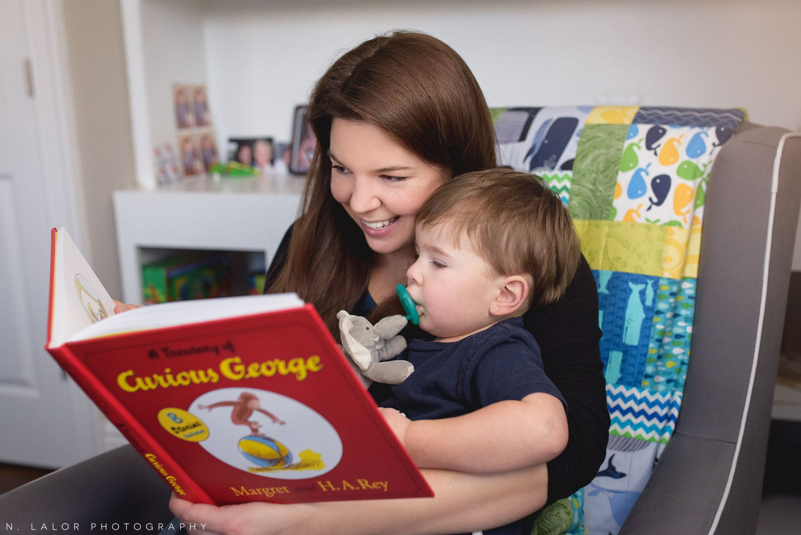 Smiling Mom reading a Curious George book to her toddler son. Lifestyle portrait by N. Lalor Photography. Connecticut.