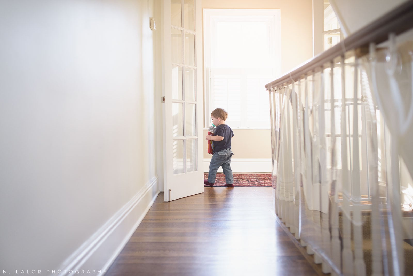 Toddler boy running off with his favorite book. In-home lifestyle photo by N. Lalor Photography. Norwalk, Connecticut.