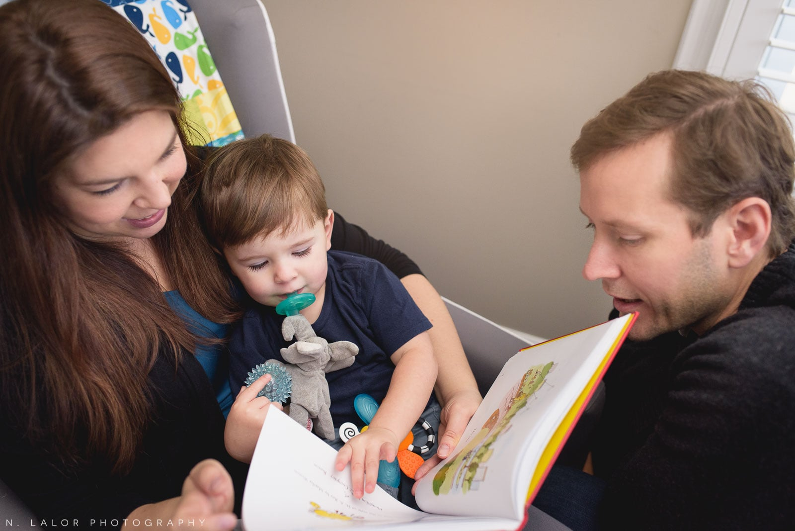 Mom and Dad reading a book to their toddler son. Lifestyle in-home portrait by N. Lalor Photography.