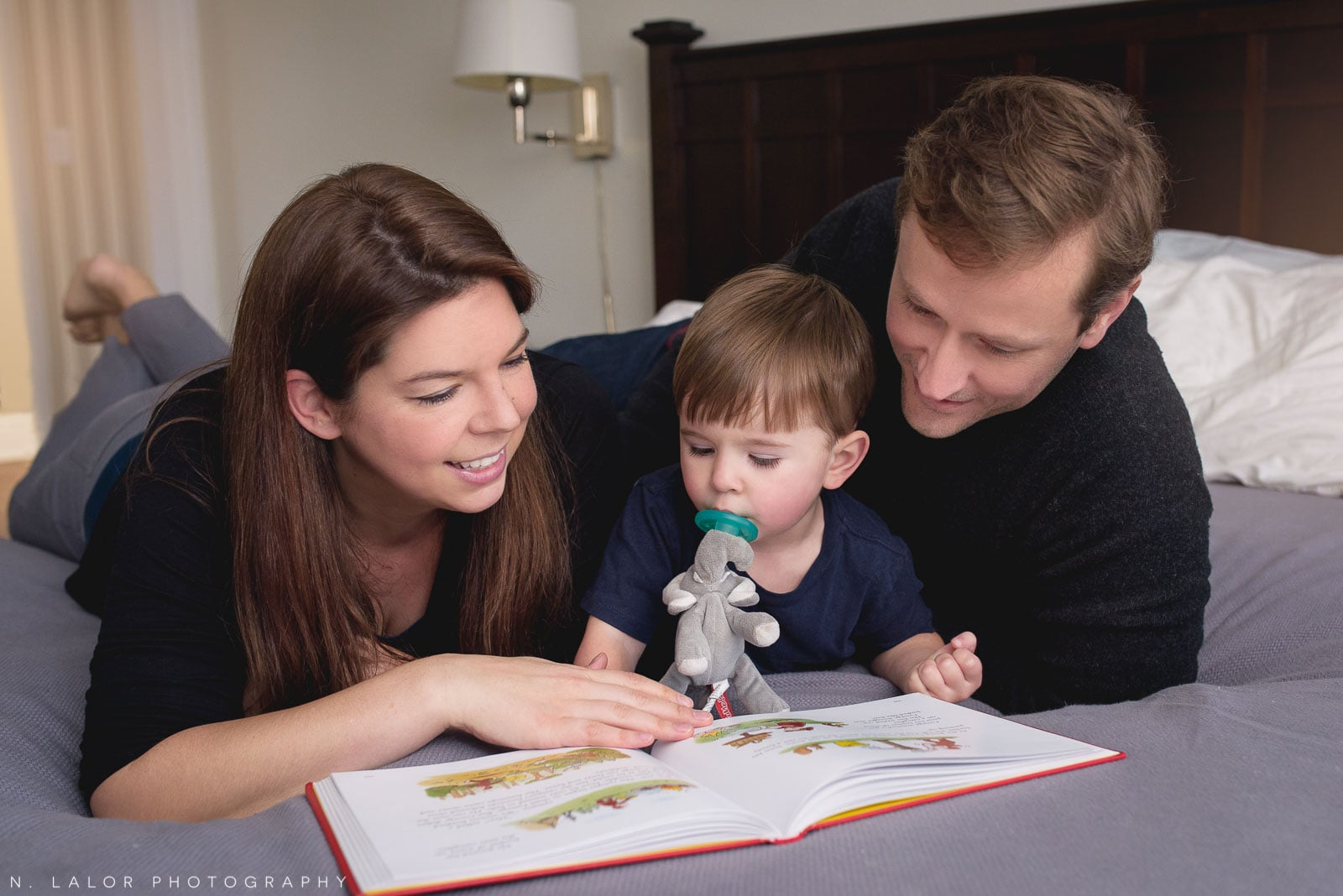 A family reading Curious George book to their toddler. Lifestyle portrait by N. Lalor Photography.