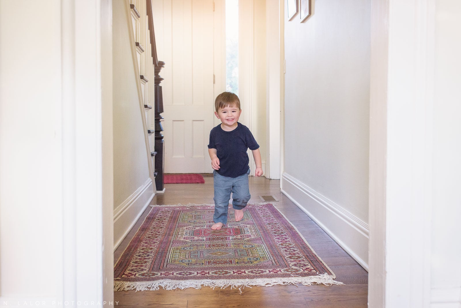 Toddler running down the hallway and laughing. Lifestyle portrait by N. Lalor Photography. Norwalk, CT.