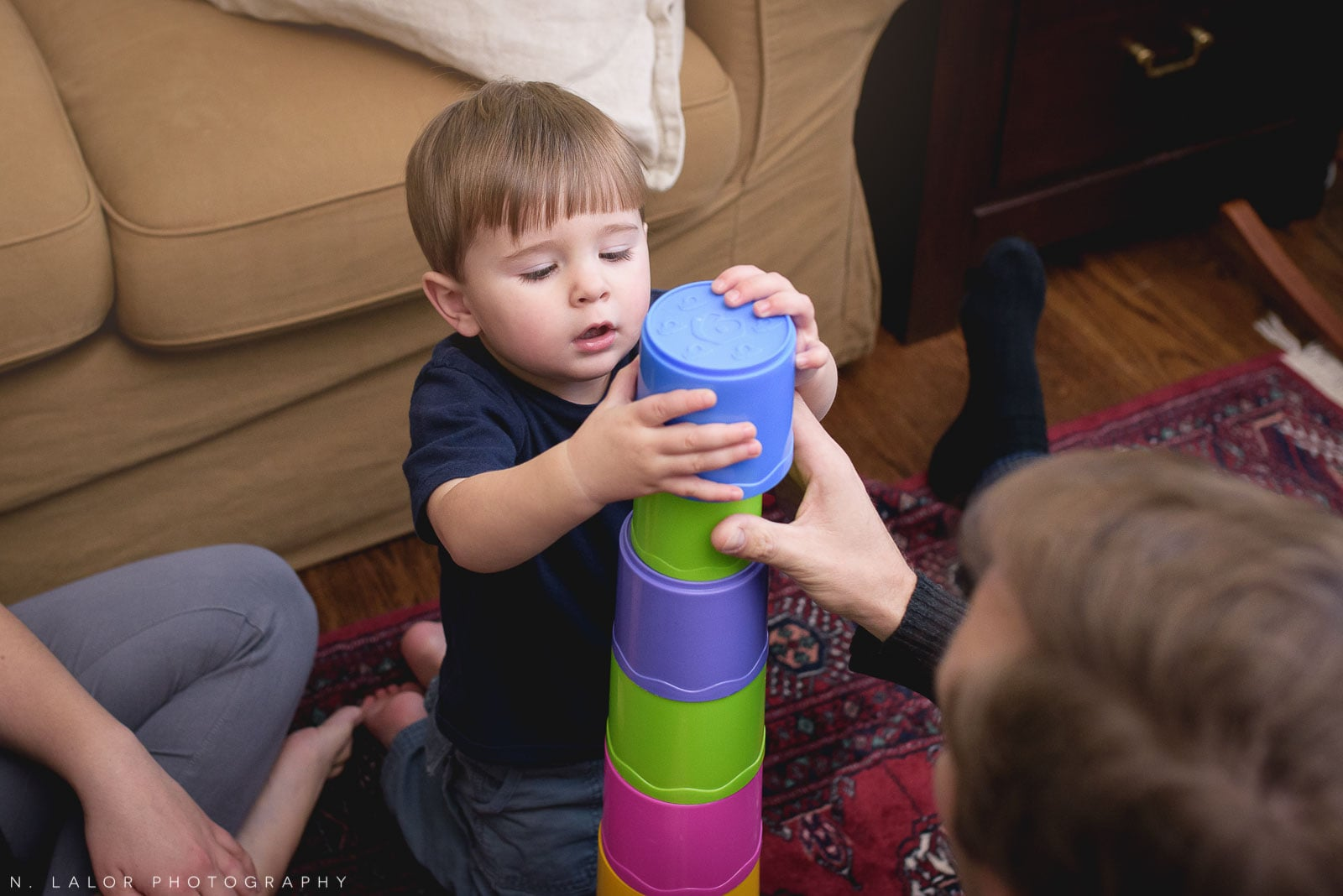 2-year old toddler playing with stacking cups. Lifestyle portrait by N. Lalor Photography. Connecticut.