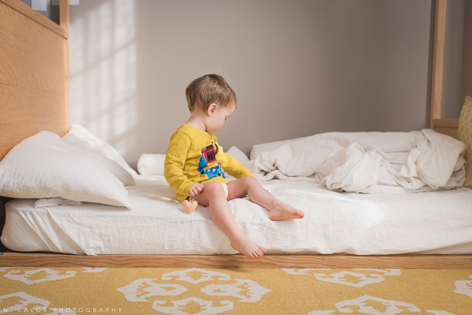 Two year old toddler sitting on his bed and holding a little felt heart ornament. Photo by N. Lalor Photography.