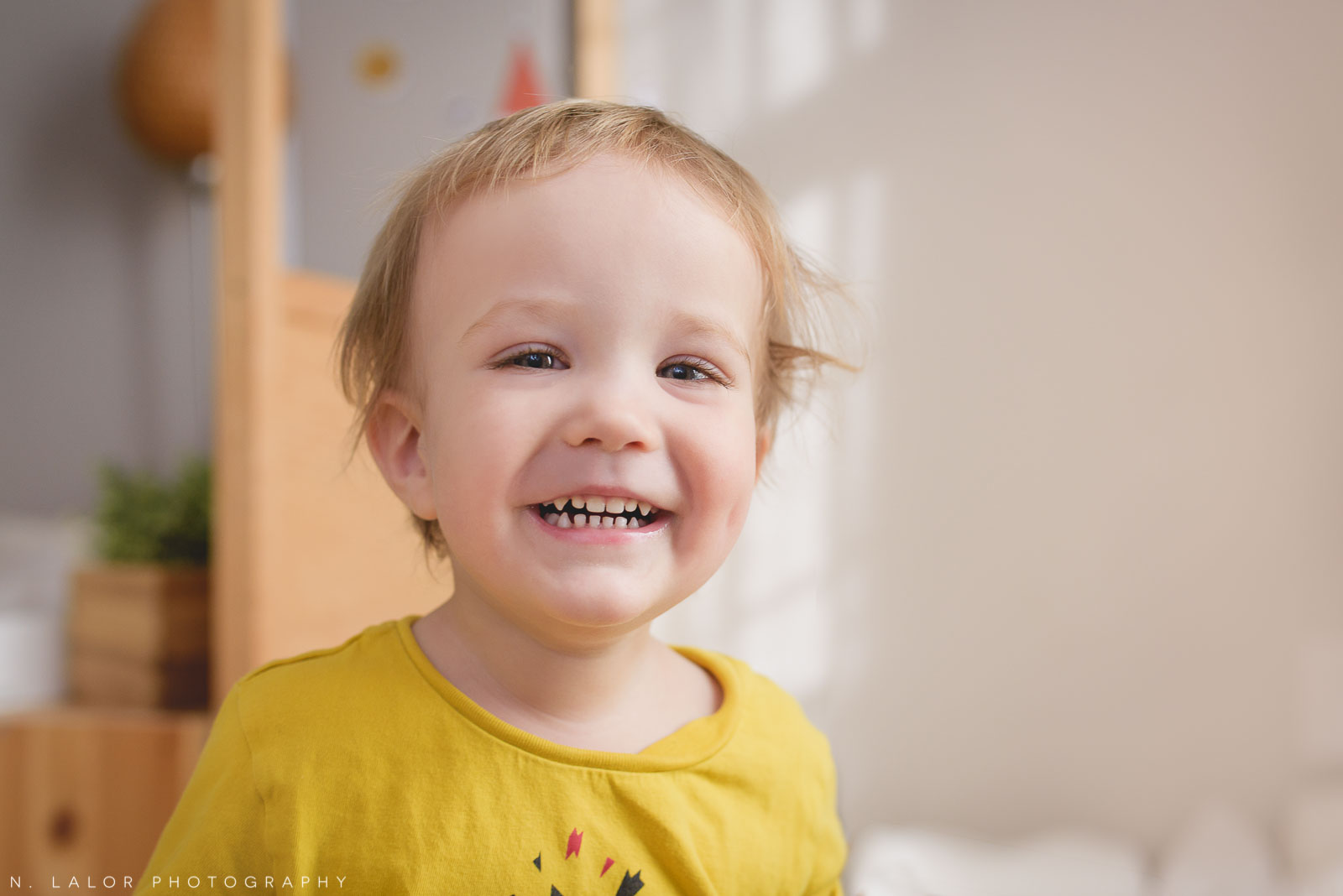 Smiling happy two year old boy in his room. Photo by N. Lalor Photography.
