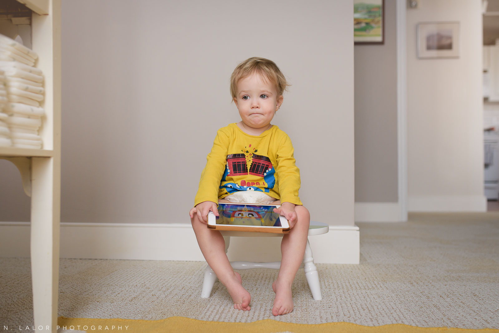 What a funny face! Two year old toddler sitting on a stool in his room, with an iPad. Photo by N. Lalor Photography.