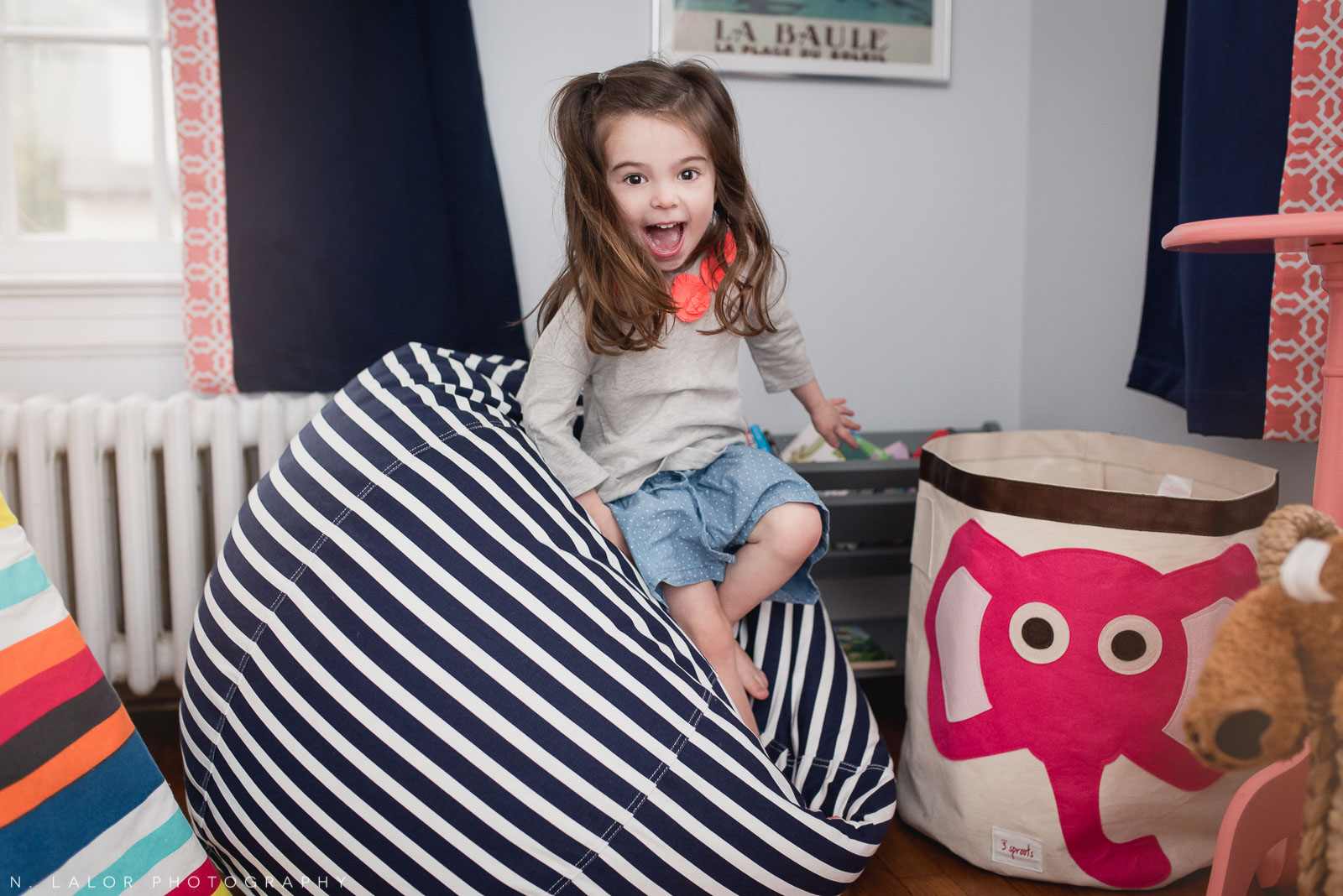Playing around in her room, a lifestyle editorial portrait of a 3-year old girl. Photo by N. Lalor Photography.