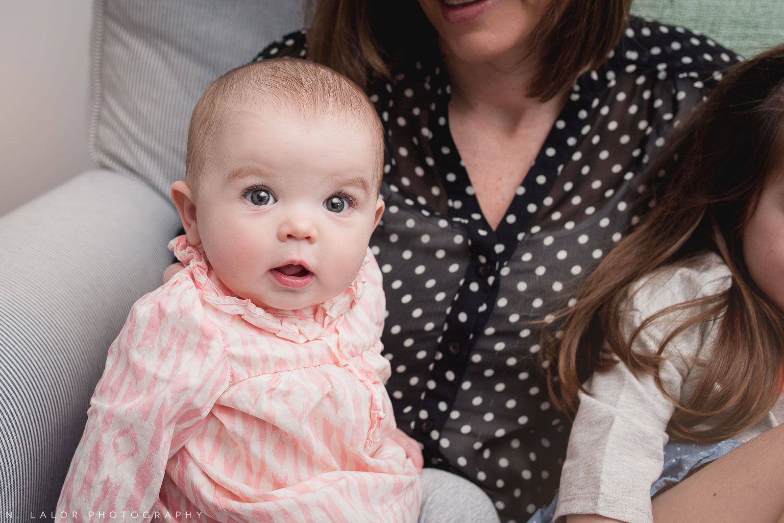 Adorable portrait of an 8-month old baby girl in Moms arms. Casual lifestyle portrait by N. Lalor Photography.