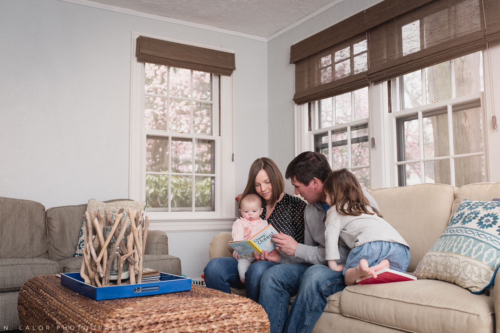 The family reading together in the Living Room. Lifestyle documentary portrait by N. Lalor Photography. Greenwich, Connecticut.