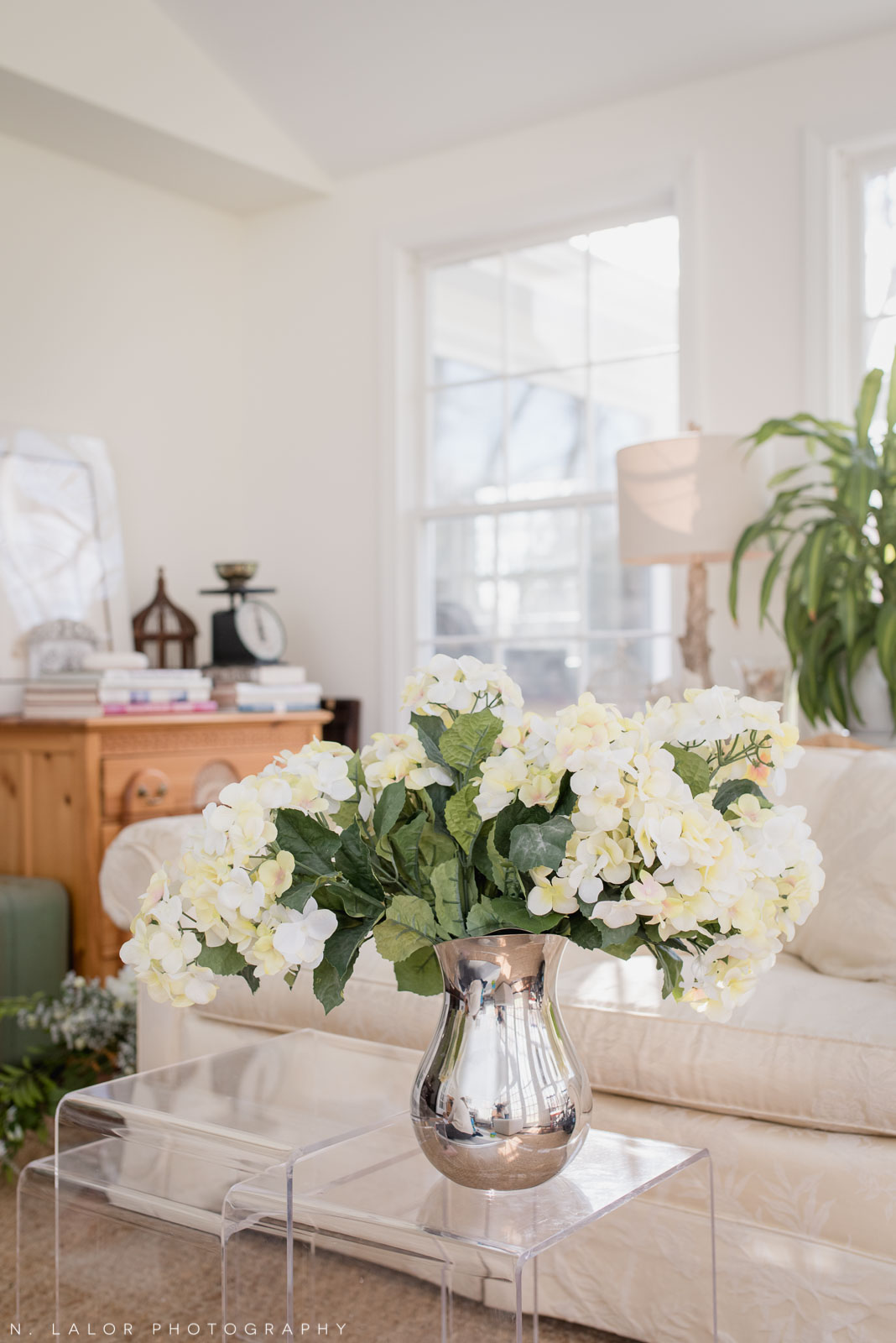 Family session interior details - flowers on nesting acrylic side tables. Photo by N. Lalor Photography.