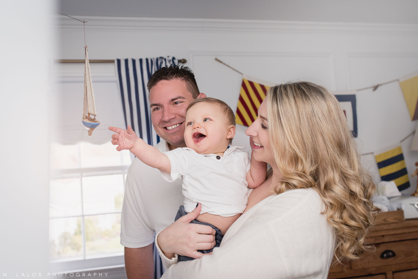 Parents holding their baby boy as he plays with a boat mobile above his crib. Image by N. Lalor Photography.