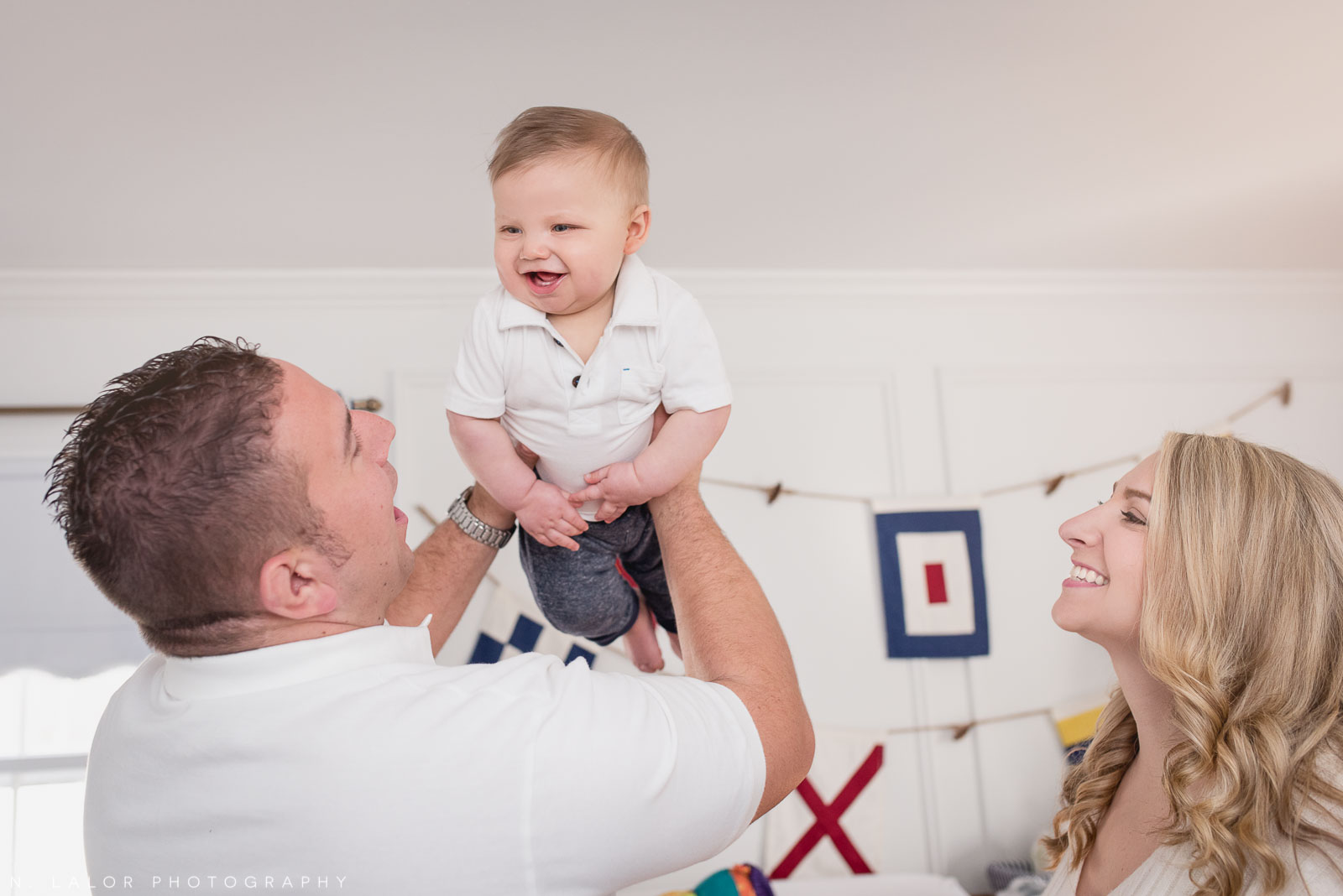 Happy baby boy with his parents. Lifestyle family photo by N. Lalor Photography.