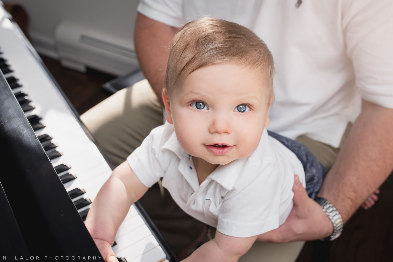 Editorial portrait of 8-month baby boy playing piano with Dad. At-home family session with N. Lalor Photography. Fairfield County, CT.