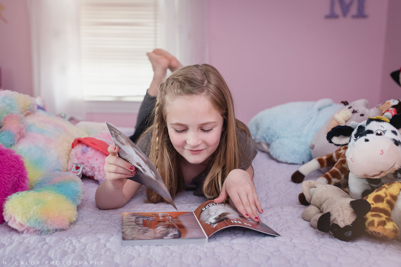 Tween girl reading a book on her bed. Editorial-style family session by N. Lalor Photography.