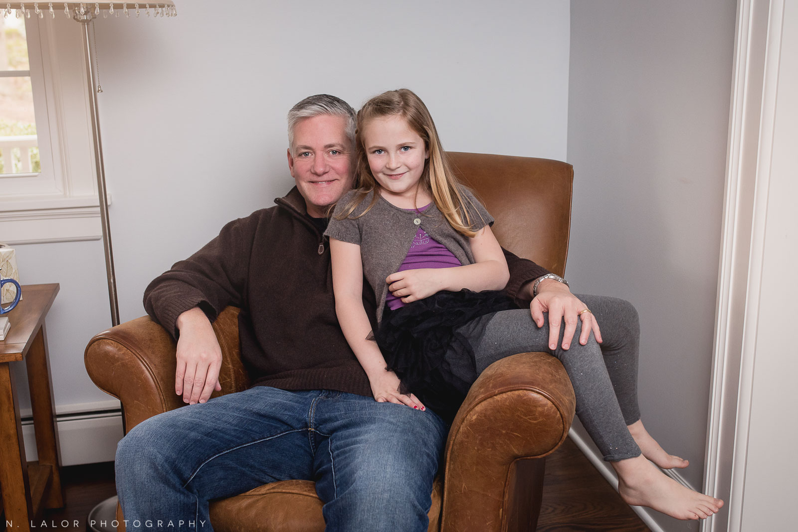 Father with his 7-year old daughter, at home, sitting in his armchair. Family photo session by N. Lalor Photography.