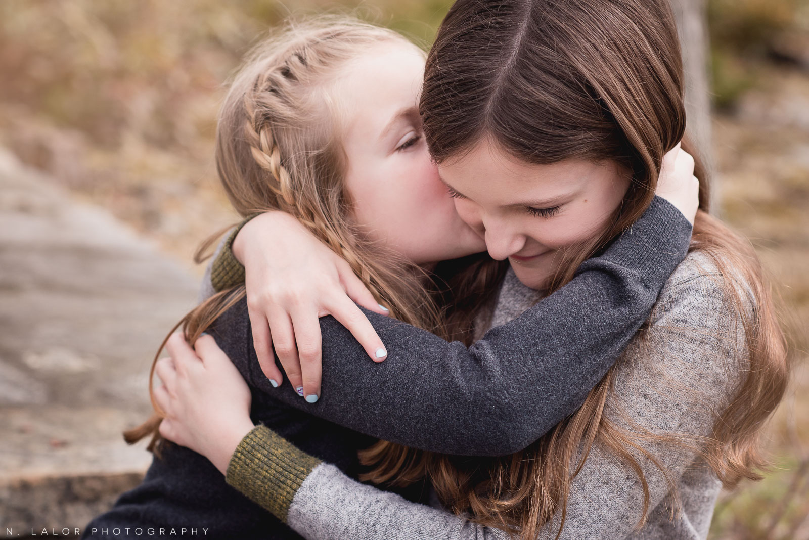 Little sister giving big sis a kiss. Lifestyle family portrait by N. Lalor Photography.