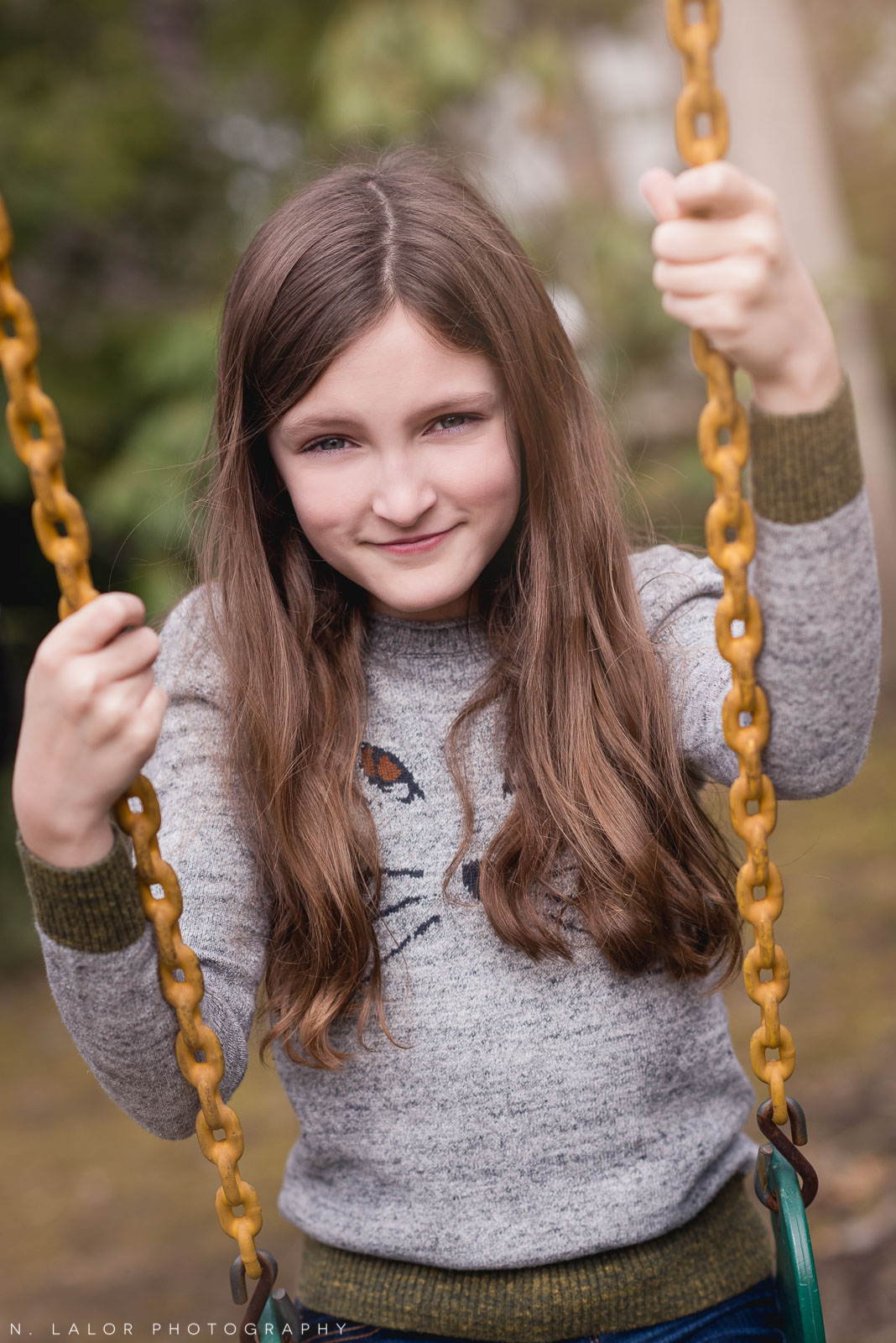 Lifestyle portrait of a tween girl on a swing by N. Lalor Photography. Darien, CT.