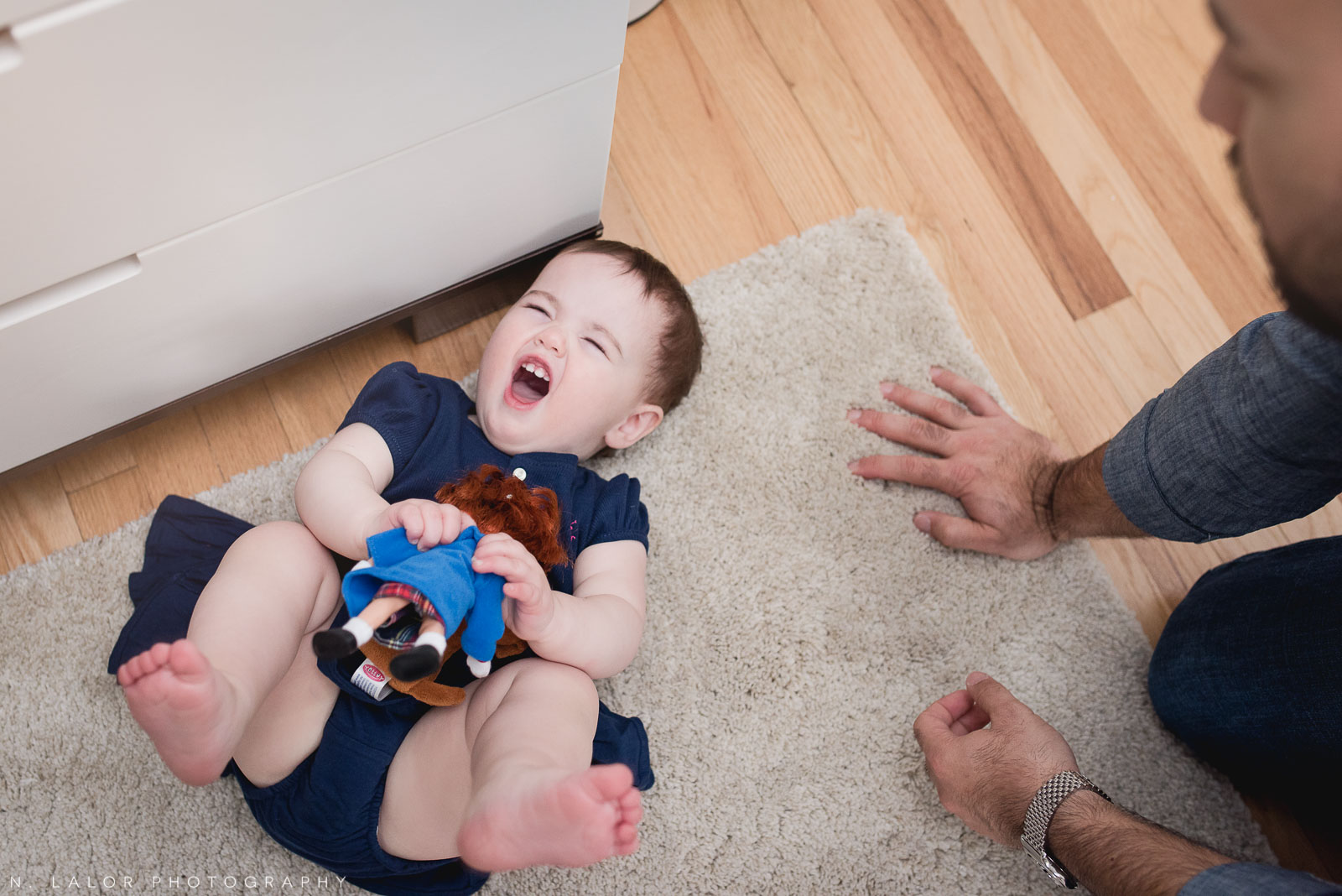 1-year old tantrum while holding a Madeline doll. Lifestyle family photograph by N. Lalor Photography.