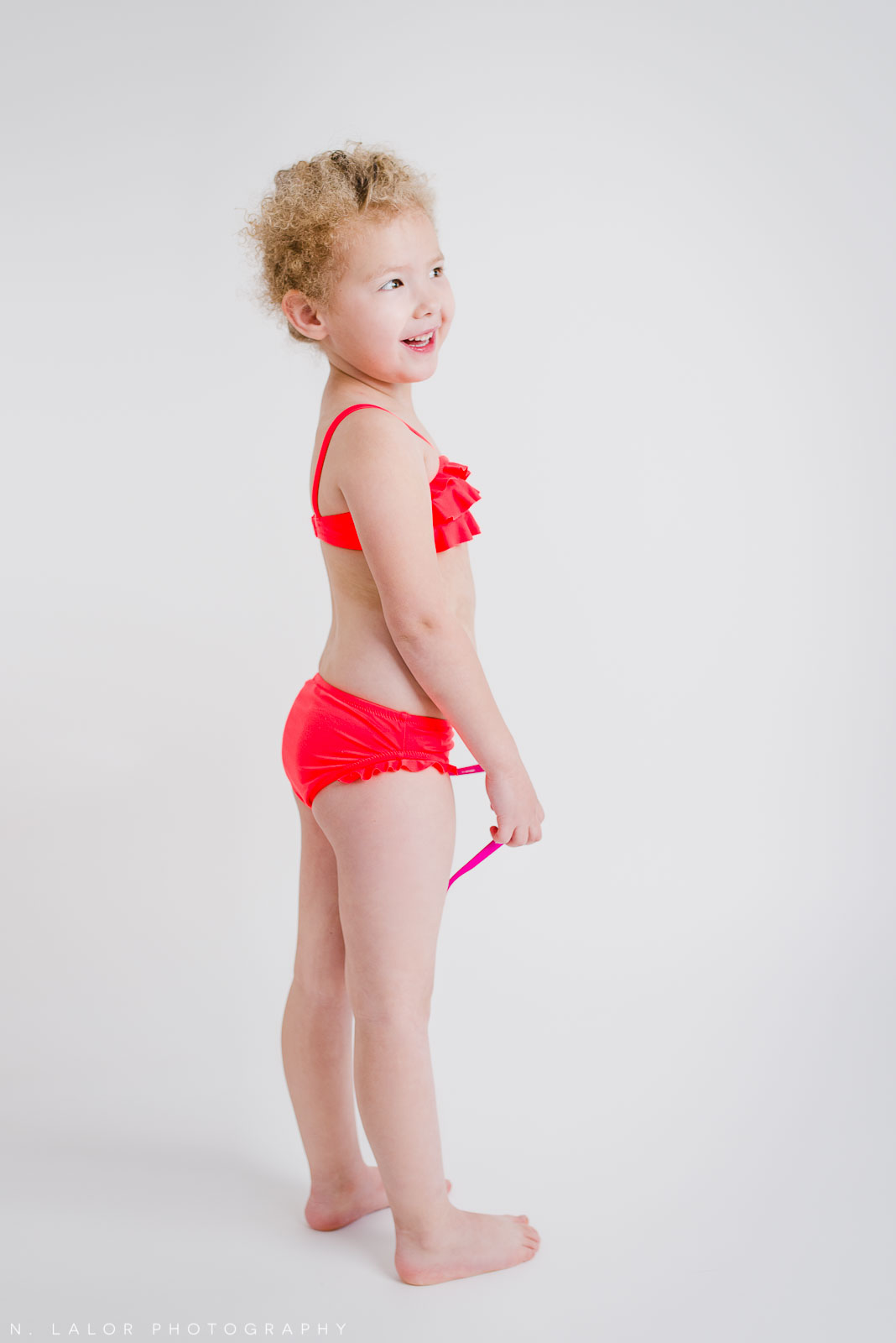 Simple and fun studio portrait of a 4-year old girl wearing a red swim suit. By N. Lalor Photography. Greenwich, CT.