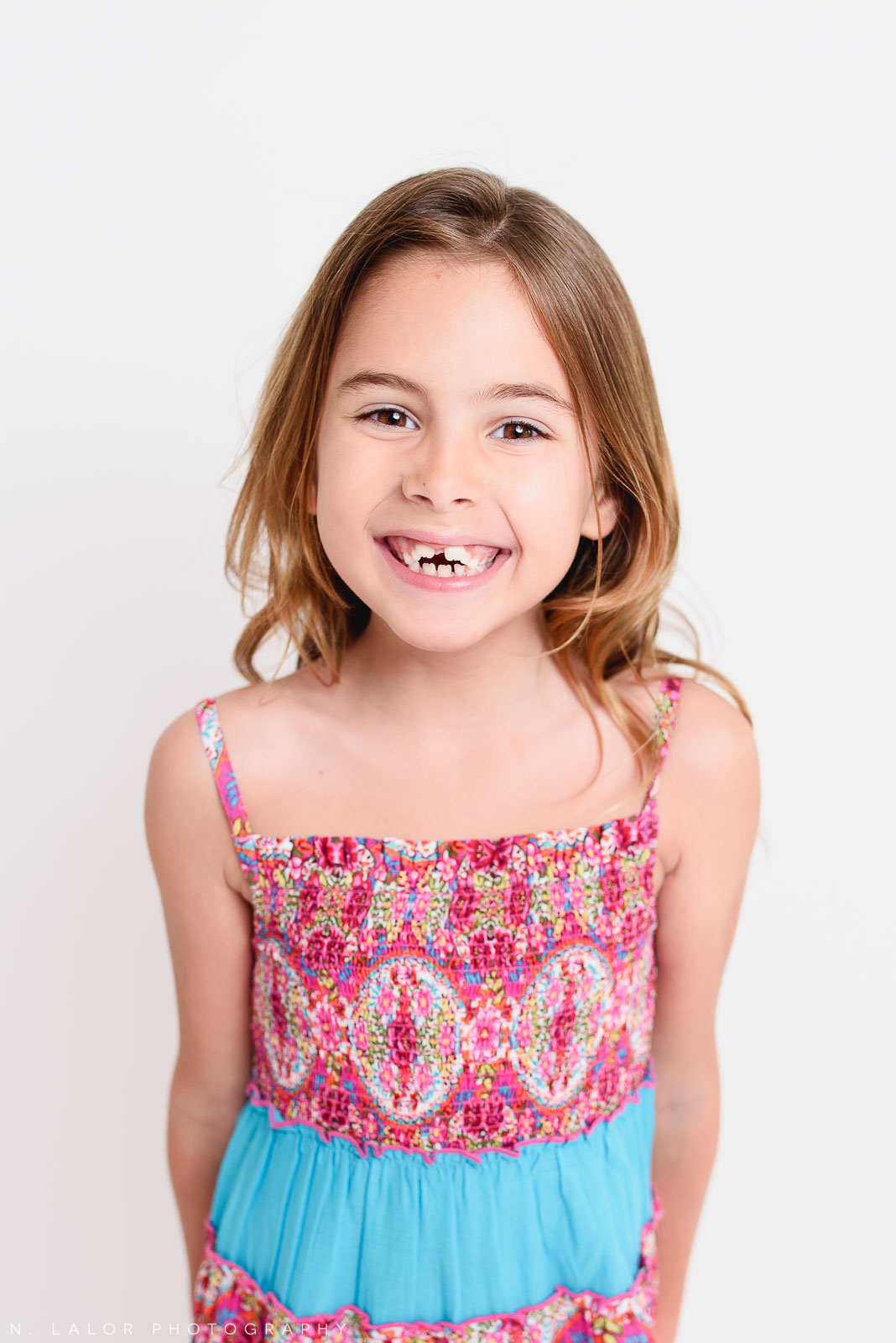 Simple, clean, smiling photo! Editorial studio portrait of 6-year old girl by N. Lalor Photography in Greenwich, Connecticut.