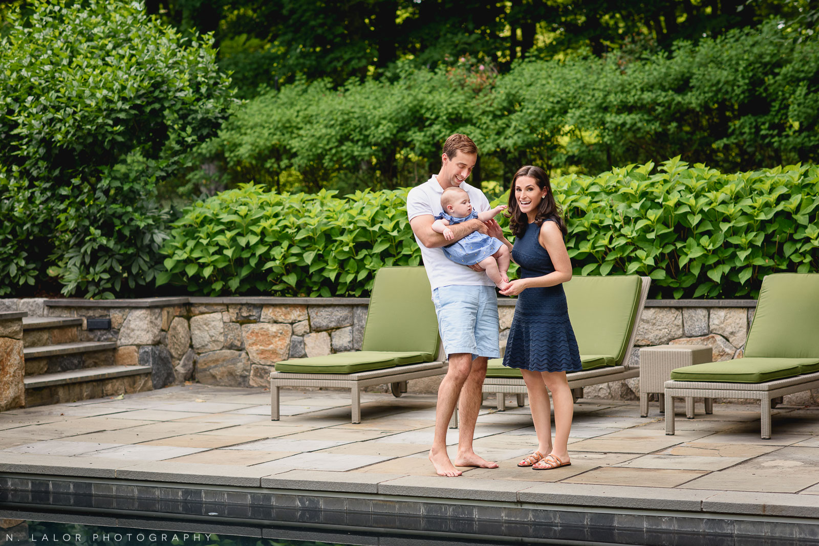 Happy family by the pool in the back yard. In-home family session with N. Lalor Photography in New Canaan, CT.