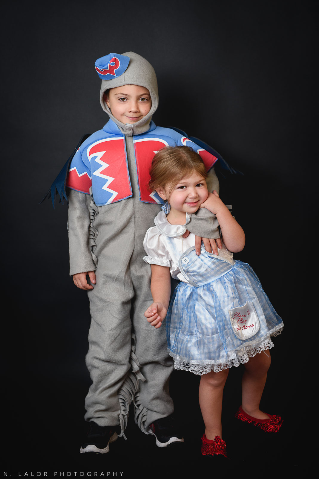 Dorothy and a flying monkey. PJ Masks. Kids Halloween costume portrait by N. Lalor Photography in Greenwich, Connecticut.