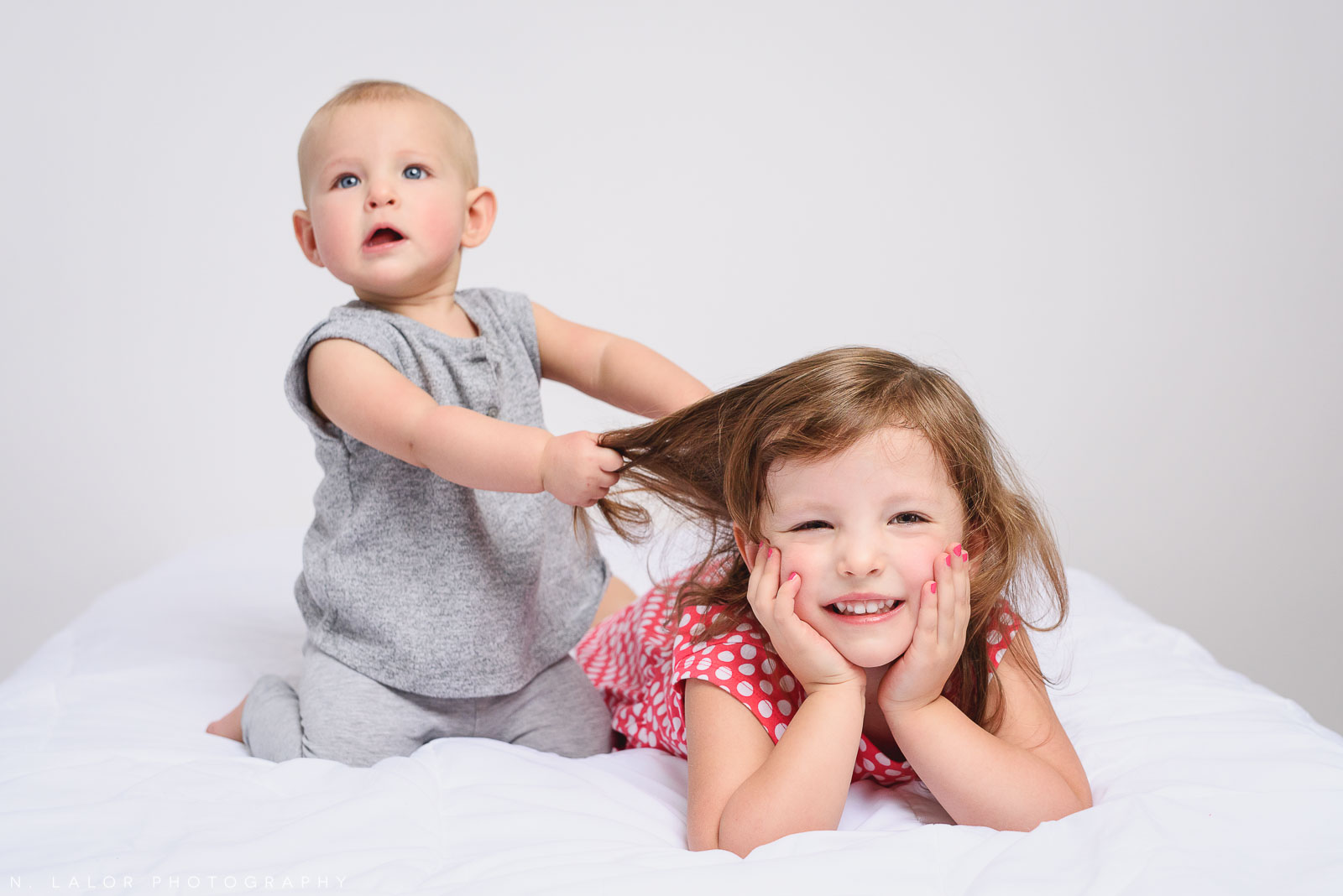 The reality of having a little sister. Simple studio portrait by N. Lalor Photography in Greenwich, Connecticut.