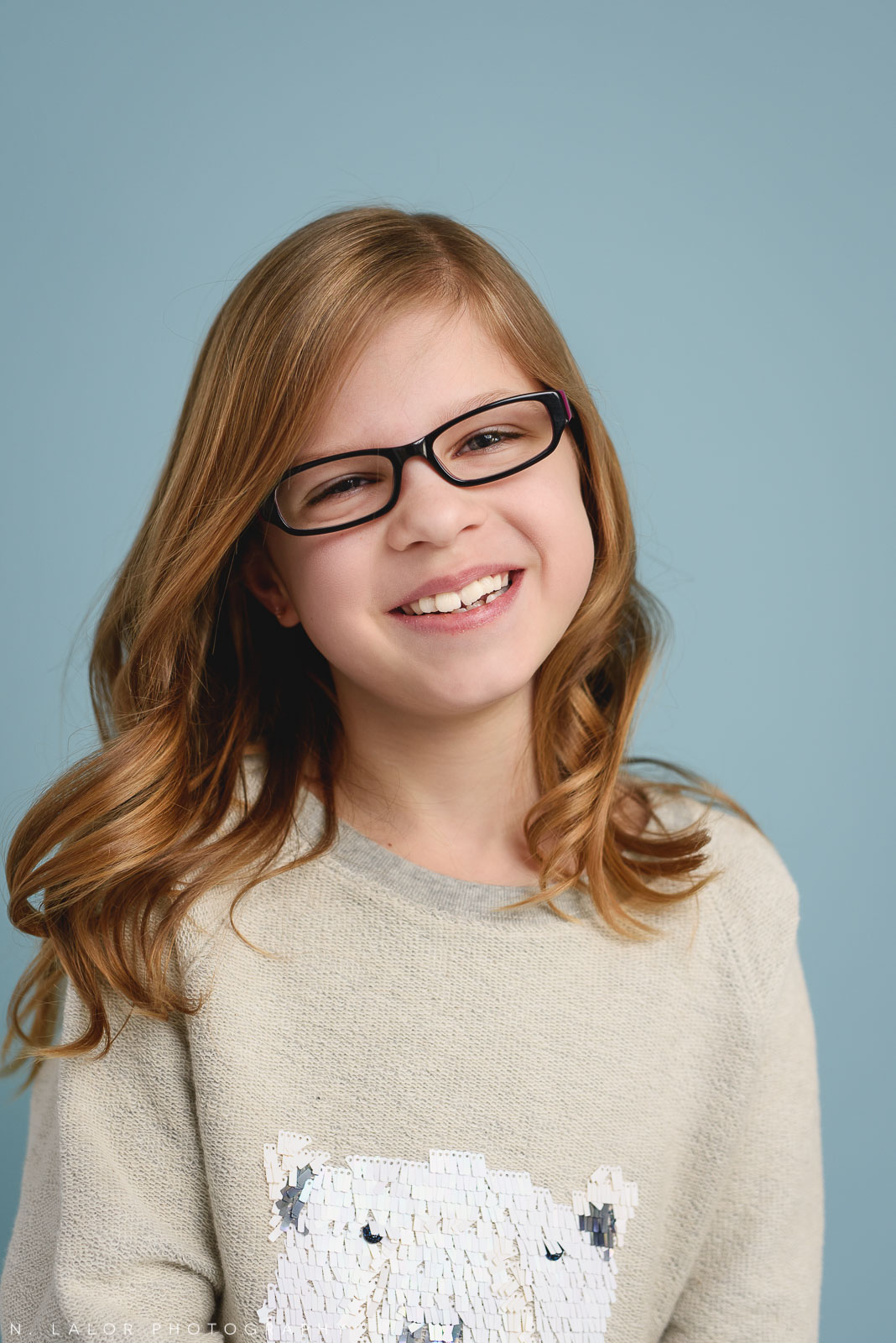 Tween girl with glasses. Tween photo session with N. Lalor Photography. Studio located in Greenwich, Connecticut.