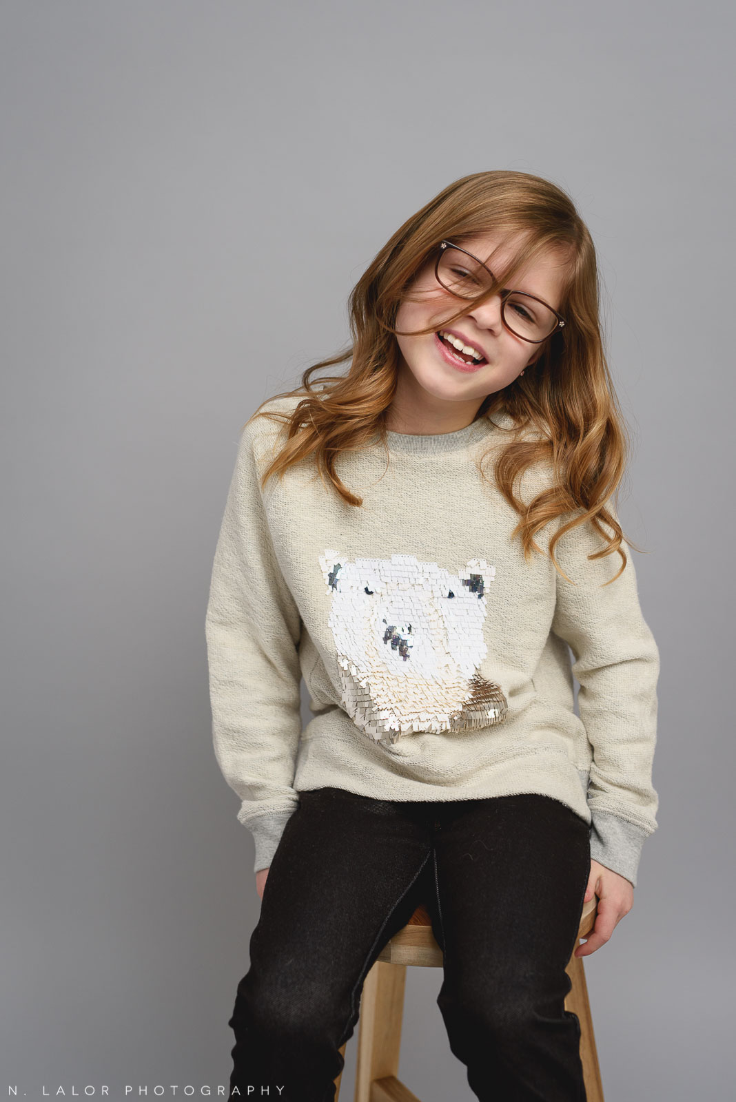Her favorite sweater. Tween photo session with N. Lalor Photography. Studio located in Greenwich, Connecticut.