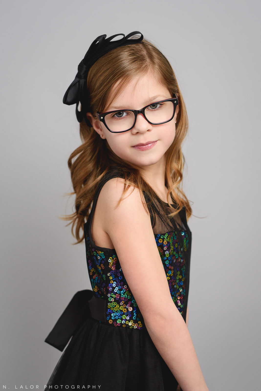 Black sparkle dress with bow headband. Tween photo session with N. Lalor Photography. Studio located in Greenwich, Connecticut.