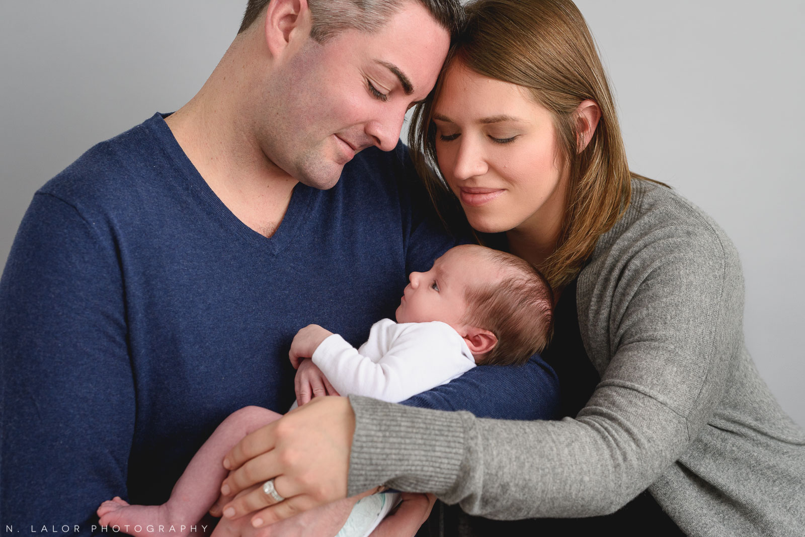 Parents together with their new baby boy. Newborn photo session by N. Lalor Photography. Greenwich, Connecticut.