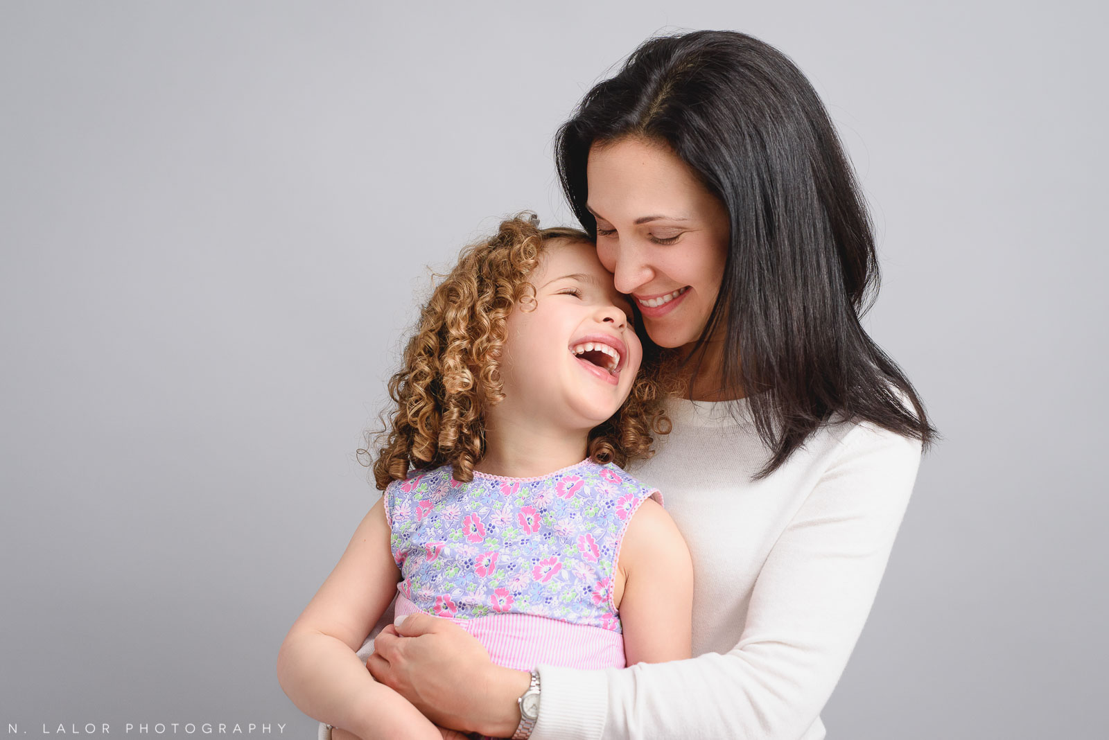 Mom and daughter laughing together. Studio family photo session with N. Lalor Photography in Greenwich, Connecticut.