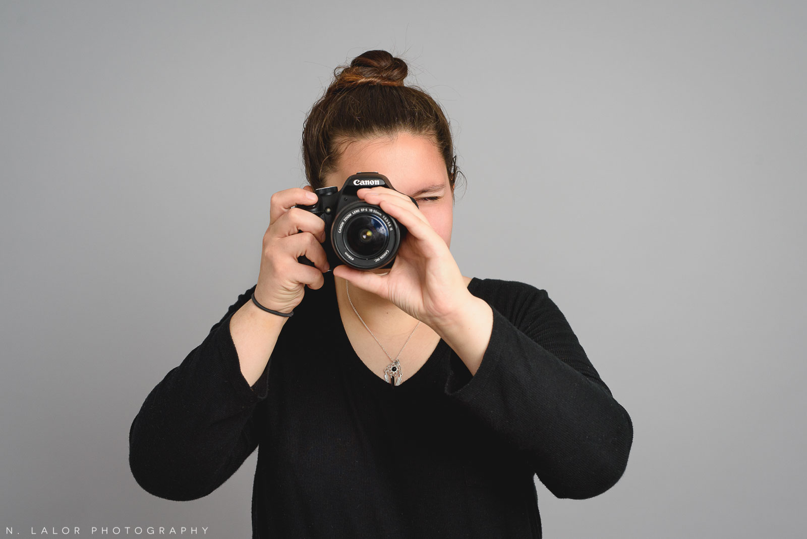 Sasha with her camera. Teen family photo session with N. Lalor Photography. Greenwich, Connecticut studio photographer.