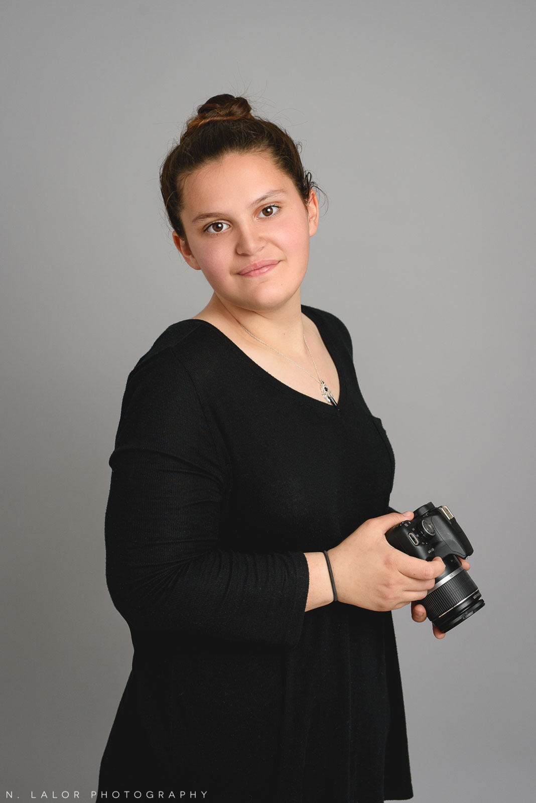 Sasha with her photo camera. Teen family photo session with N. Lalor Photography. Greenwich, Connecticut studio photographer.