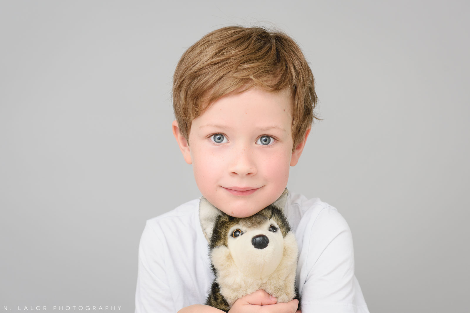 7-year old boy with his favorite stuffed toy. Simple studio portrait session with N. Lalor Photography in Greenwich, CT.