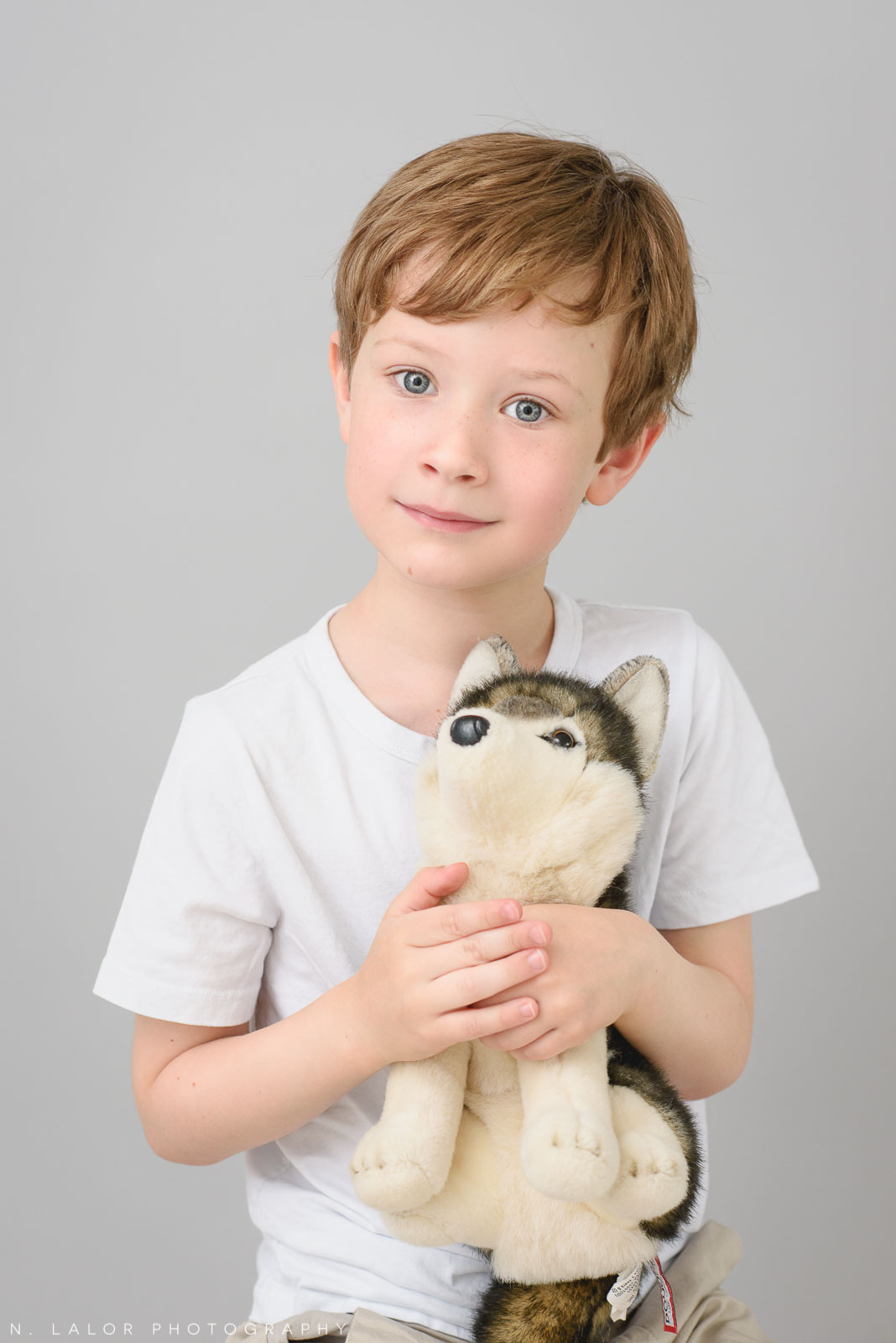 Boy with his favorite toy, Arctic Dog. Simple studio portrait session with N. Lalor Photography in Greenwich, CT.