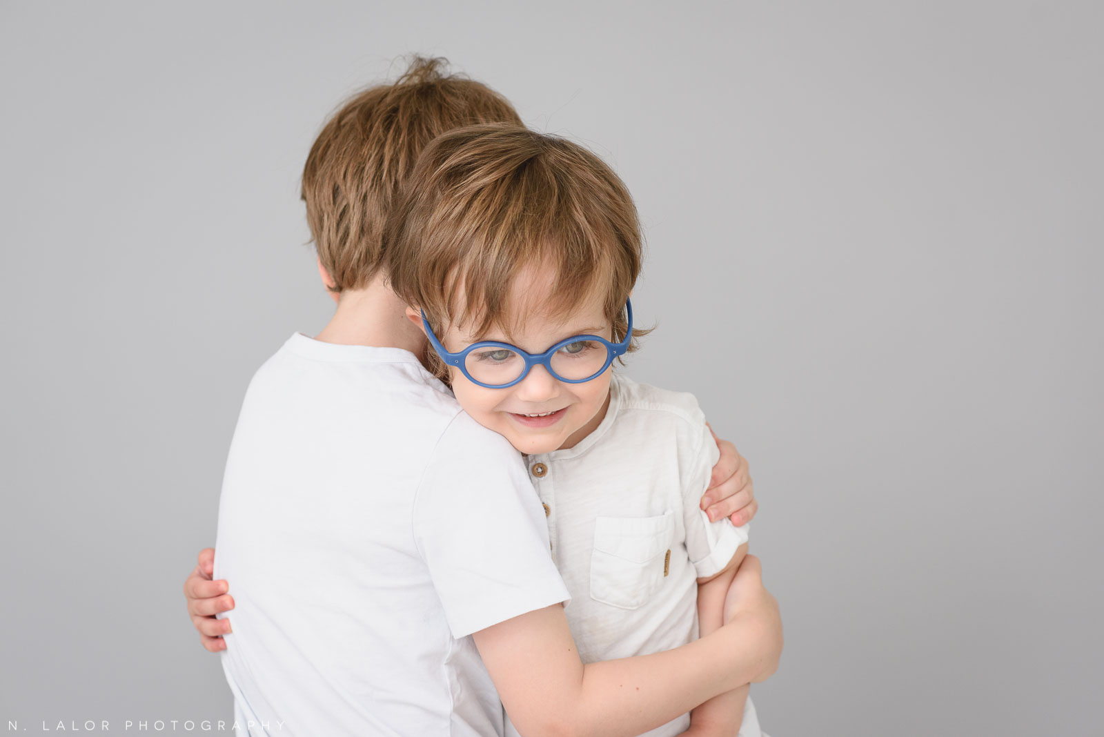 Brothers, a hug. Simple studio portrait session with N. Lalor Photography in Greenwich, CT.