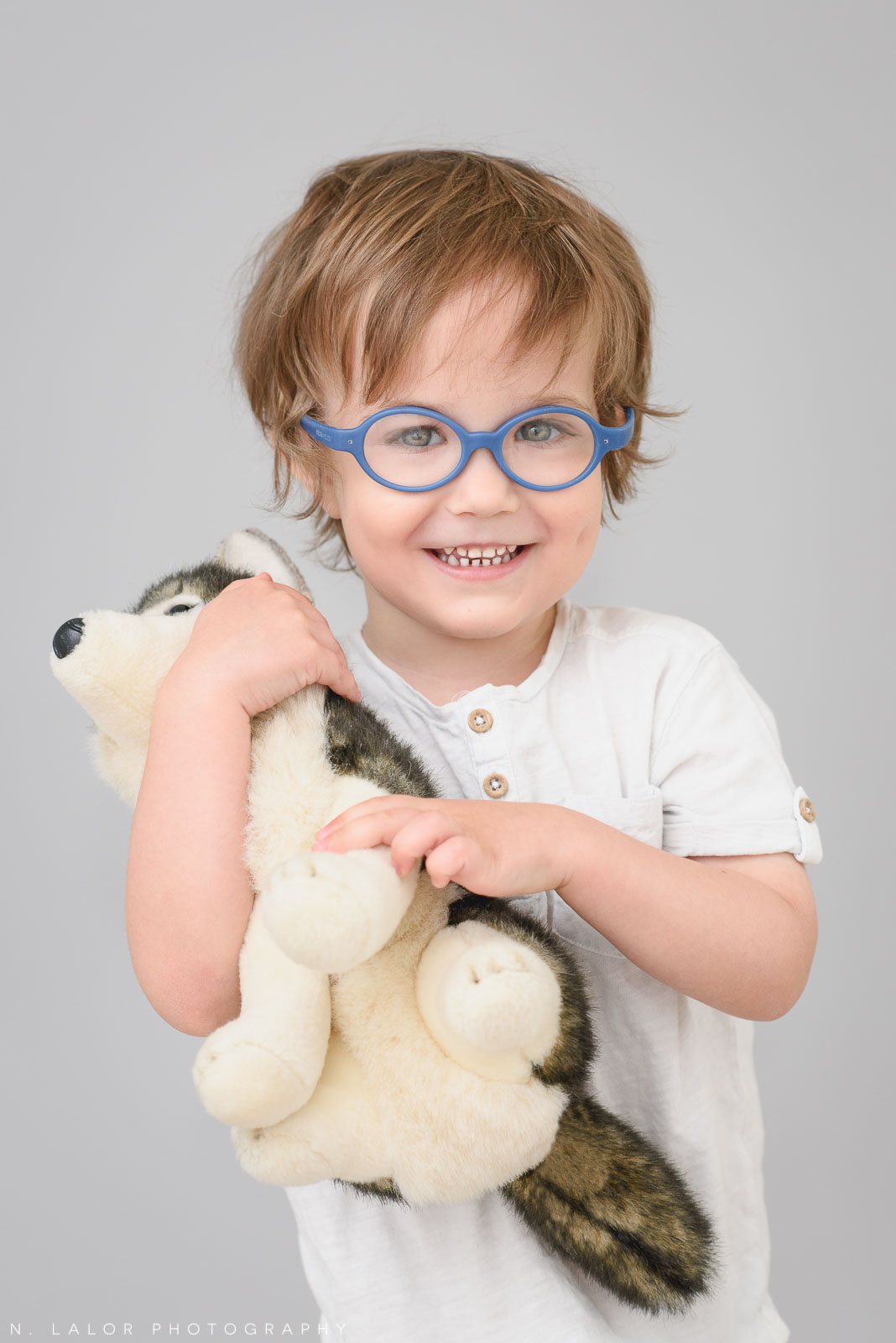 Hugging a toy dog. Simple studio portrait session with N. Lalor Photography in Greenwich, CT.