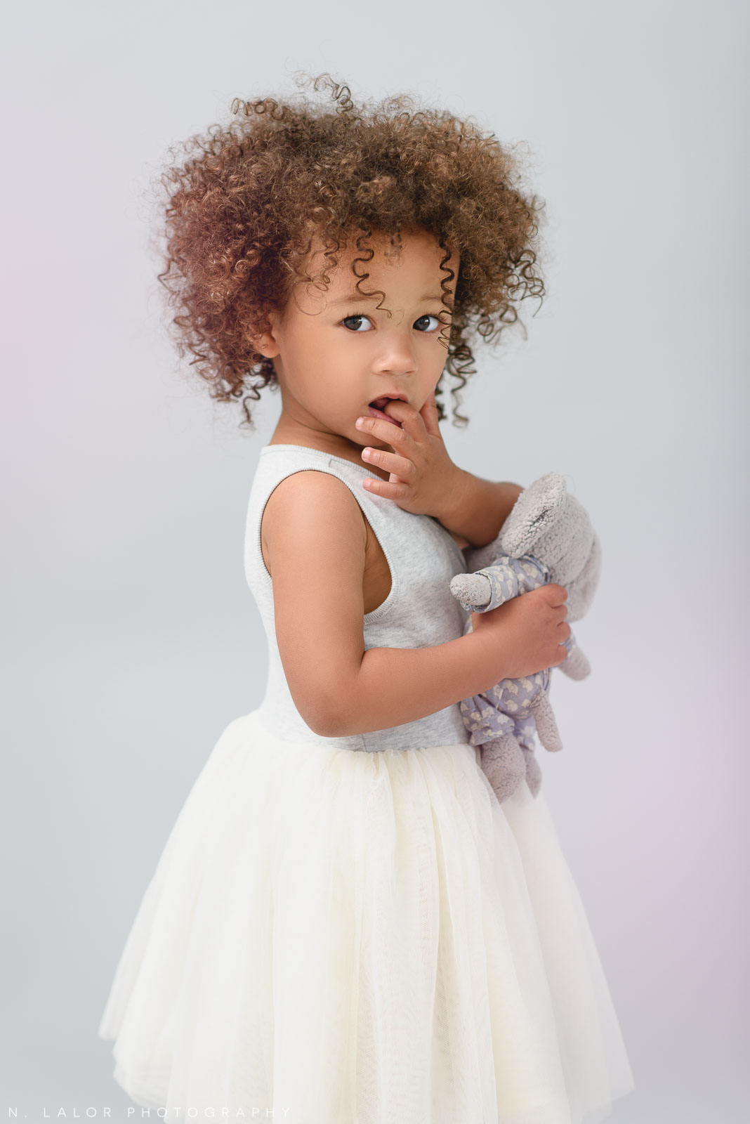 2-year old girl with her stuffed toy. Studio portrait session with N. Lalor Photography in Greenwich, Connecticut.