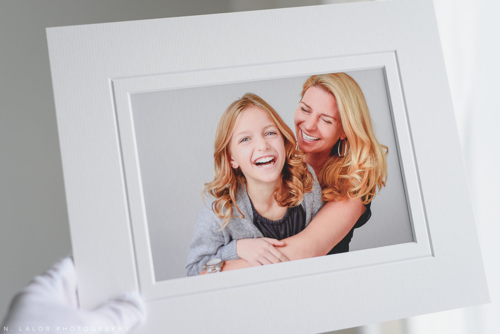 Mom laughing with daughter. Portrait by N. Lalor Photography in Greenwich, Connecticut.