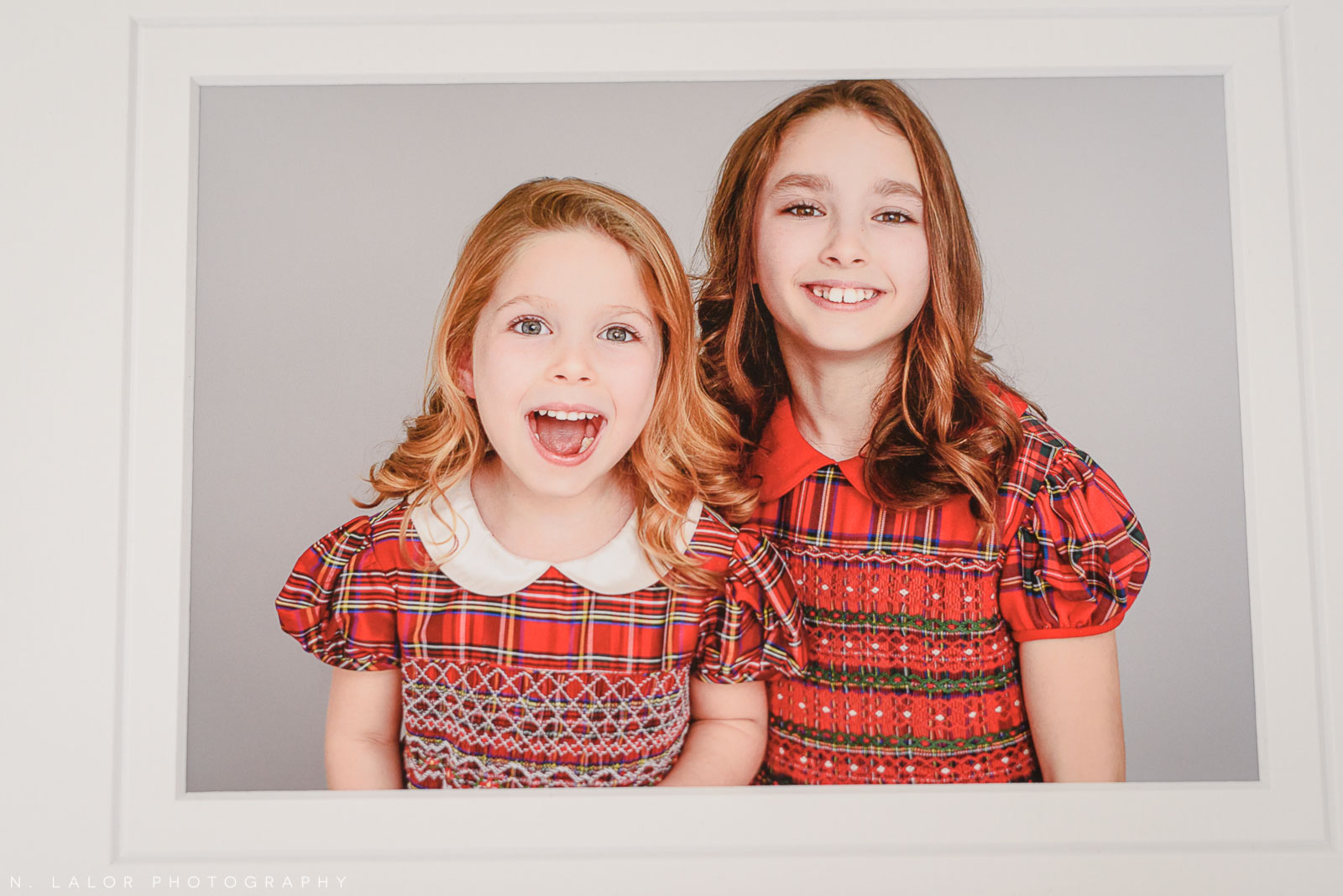 Sisters in Christmas dresses. Family photoshoot by N. Lalor Photography in Greenwich, Connecticut.