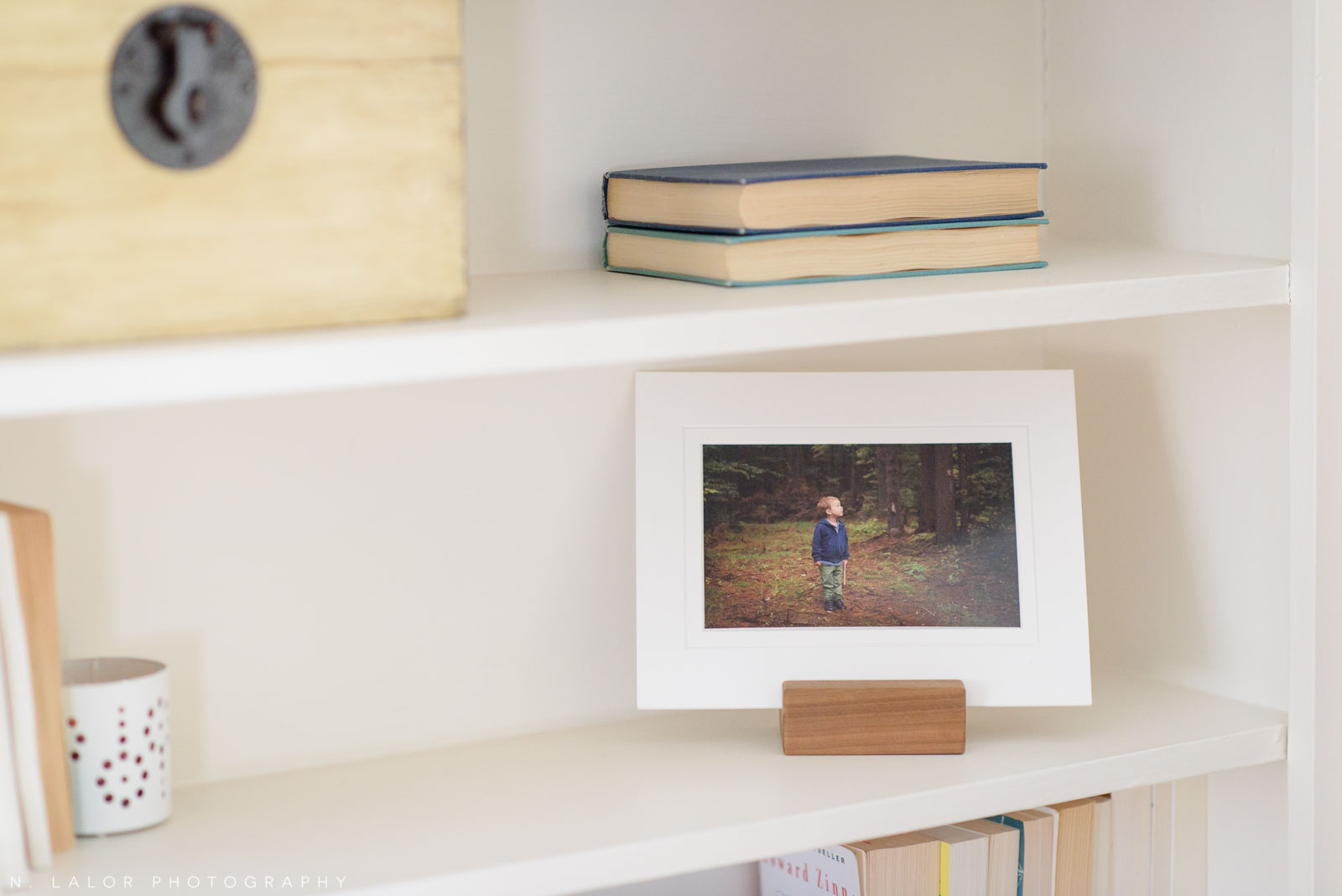 An open-shelf display of a matted photo in a wood stand. Photograph by N. Lalor Photography.