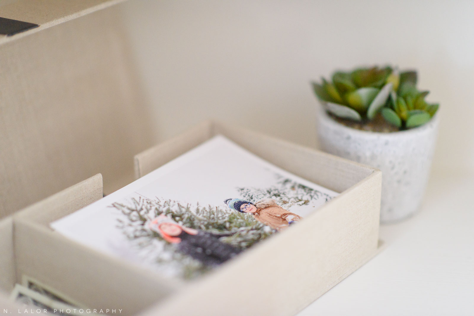 A look into a child's photo memory box, displayed on an open shelf in the living room. Photograph by N. Lalor Photography.