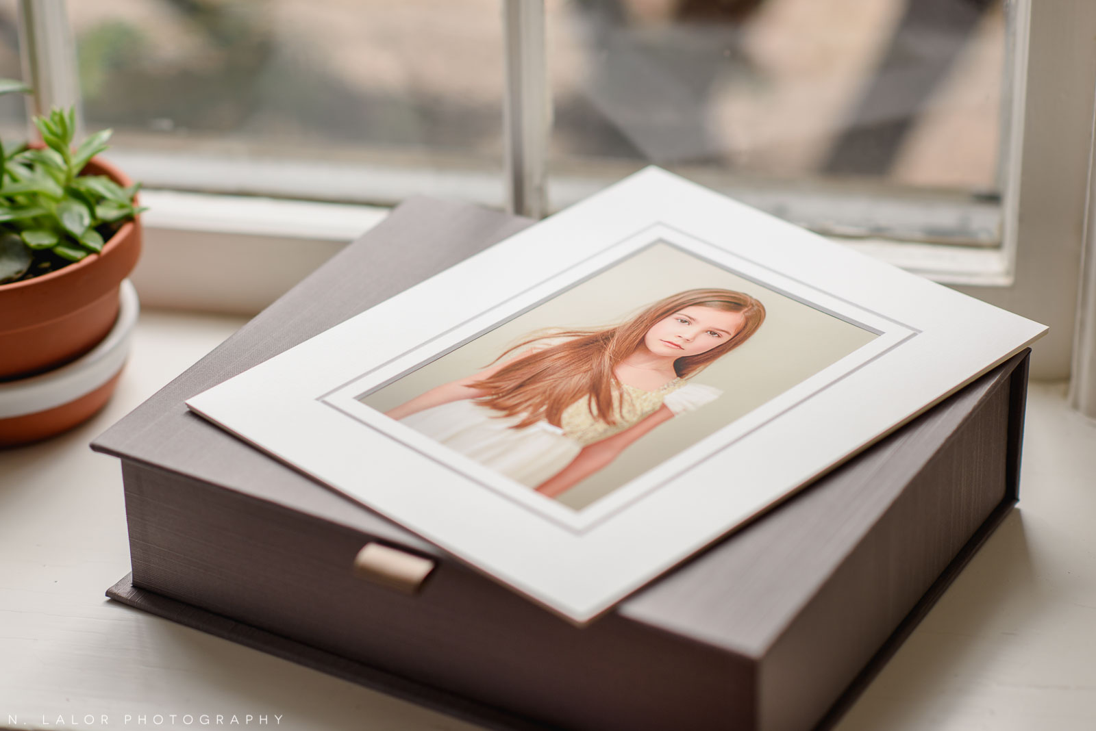 Photo of a family heirloom box and archival print in a white mat.